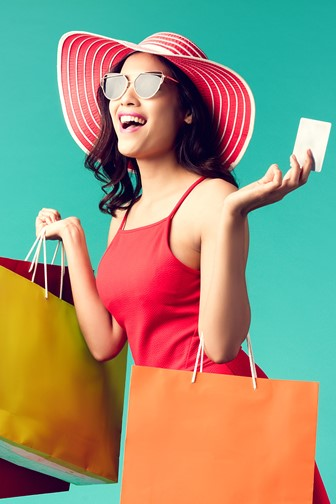 a happy young woman with a credit card and shopping bags